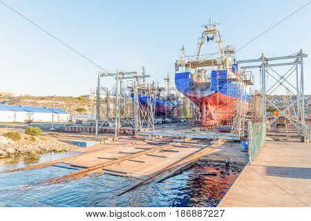 SALDANHA BAY SOUTH AFRICA - APRIL 1 2017: Fishing trawlers being repaired on a slipway in Saldanha Bay an harbor town in the Western Cape Province