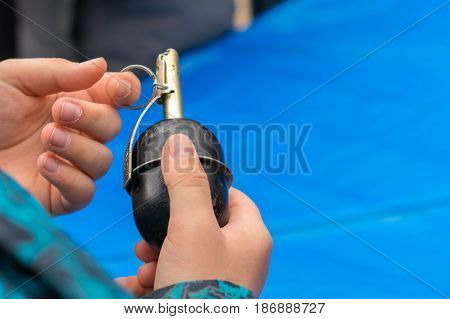 Grenade in the hands of a child and pulls a grenade pin the danger of explosion