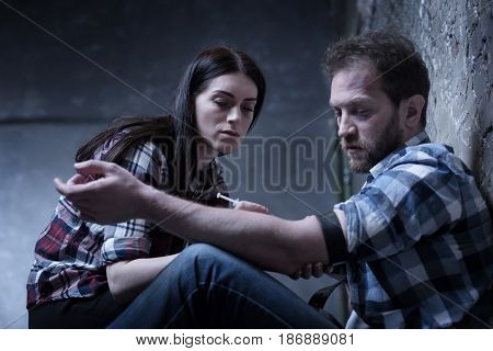 Indifference to any kind of pain. Lonely homeless obsessed couple sitting on the ground in the darkness while sharing drug dose and making syringe injection of heroin