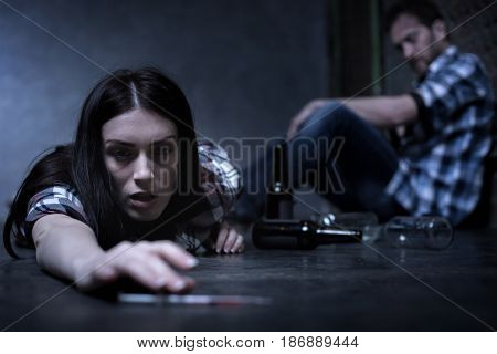 Lethal reaction to drug. Horrible overdosed exhausted woman lying on the ground at the opium den and suffering from big heroine dose while other addict siting in the background