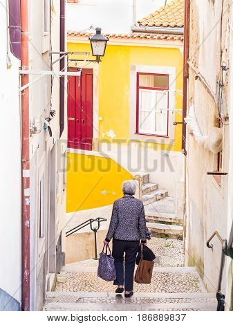COIMBRA PORTUGAL - April 04 2017: Elderly lady walking down the stairs in the old town of Coimbra in Portugal.
