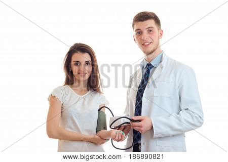 joyful young girl stands with the tonometer on the arm next to the smiling doctor smock isolated on white background