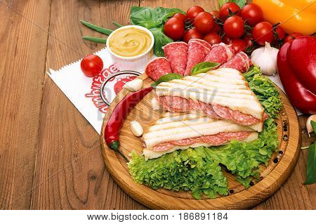 Sandwich with salami. Lettuce cherry tomatoes mustard basil garlic on wooden background. Rustic stale.