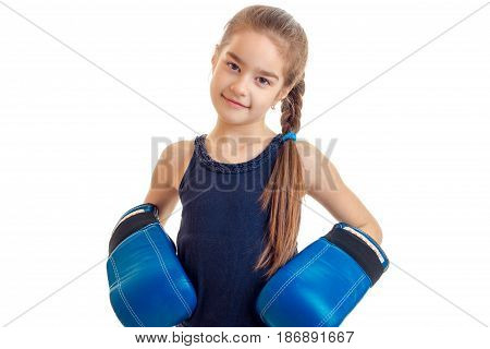 cute little baby-girl standing in front of the camera in big boxing gloves is isolated on a white background close-up