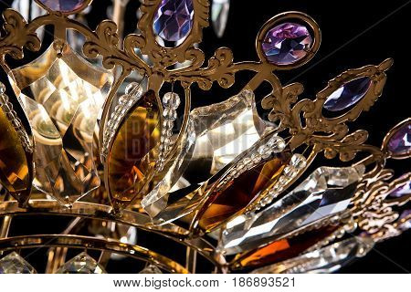 Contemporary gold chandelier isolated on black background. Crystal chandelier decorated purple crystals. close-up