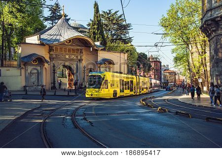 ISTANBUL TURKEY - MAY 2 2017: Yellow modern tram on the historical street moving from the Gulhane station against Fatih Bab Ali Osman gate background