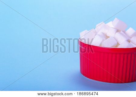 Sugar cubes in a plate with an empty space for text copy paste. On a blue background