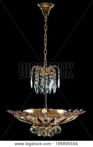 Contemporary gold chandelier isolated on black background. Crystal chandelier decorated purple crystals.