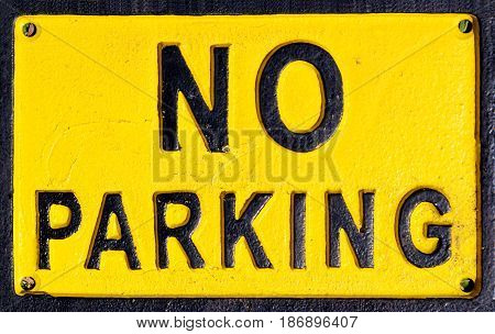 Black and yellow no parking sign for vehicles.