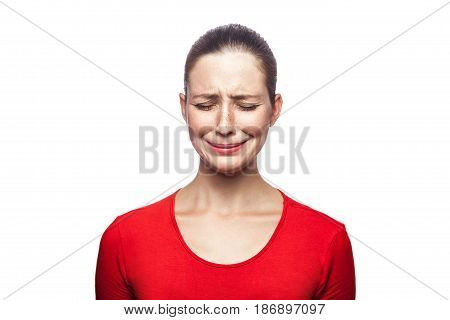 Portrait of sad unhappy crying woman in red t-shirt with freckles. closed eyes studio shot. isolated on white background.