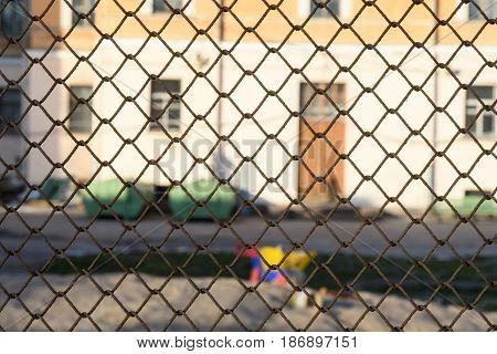 Behind The Fence, Desolate Children's Playground Near A Residential House In The Daytime