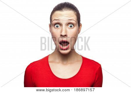 Portrait of happy surprised woman in red t-shirt with freckles. looking at camera excited with big eyes studio shot. isolated on white background.