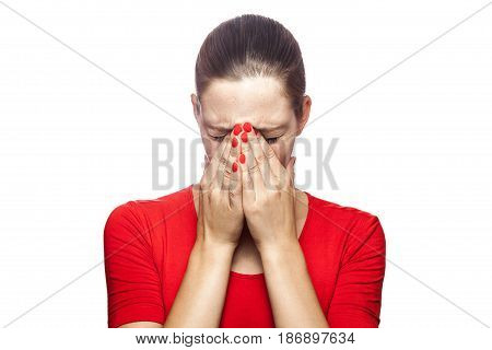 Portrait of sad unhappy crying woman in red t-shirt with freckles. closed eyes with hands studio shot. isolated on white background.