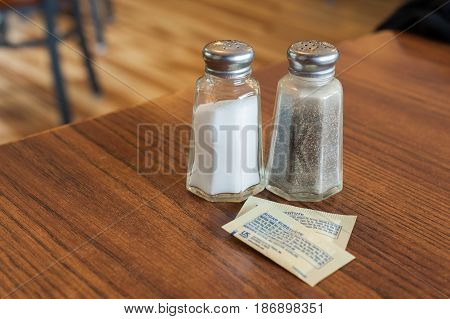 Salt and pepper sharkers and two packets of sugar substitute in a table