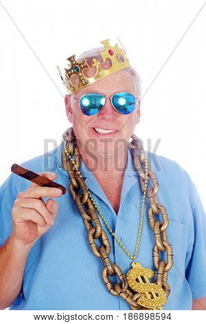 A man wears a King Crown, Gold Chains, Sunglasses and smokes a Big Cigar. Isolated on white. Room for text.