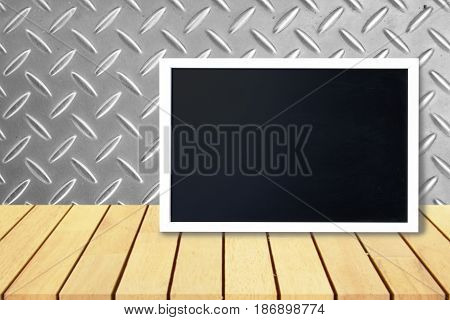 Blank black chalkboard lean on wooden table and aluminum plate pattern wall Blank copyspace for your text or design.
