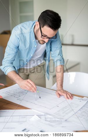 Architect working on plans at home office table and drawing