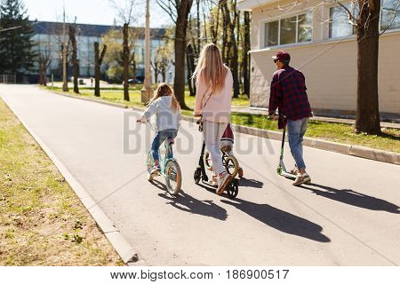 Photo from back of young couple with children on bicycles in park