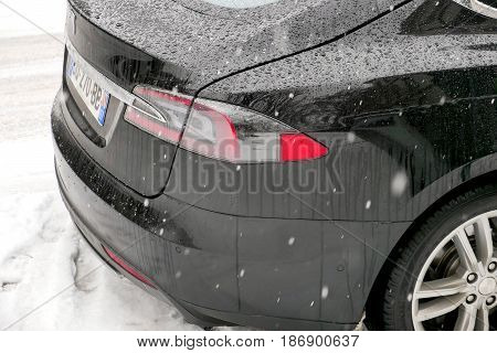 PARIS FRANCE JAN 10 2017: Snowflakes falling over Tesla hybrid electric car on a Parisian street covered with snow