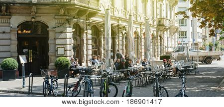 STRASBOURG FRANCE - APR 23 2017: French people and tourists anjyin a cafe and a dessert outside terrace Brant cafe in Strasbourg France