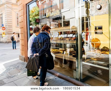 STRASBOURG FRANCE - MAY 15 2017: Two aldult women admiring the French food in the shop window of the iconic Christian pastry sweet tearoom cafe