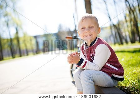 Boy sits on road at park in spring afternoon