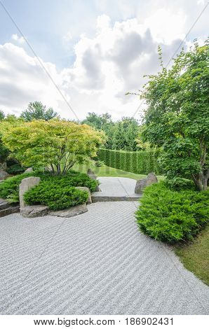 japanese zen garden with cloudy sky and green trees