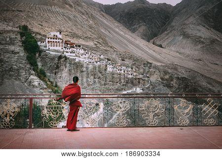 Buddhist Monk in red robe looks on Diskit Monastery Indian Himalaya Nubra Valley