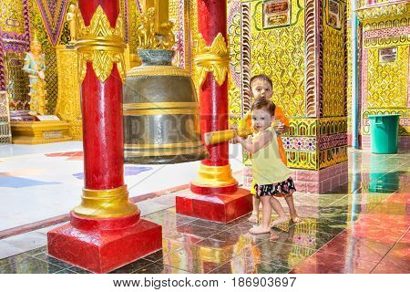 MANDALAY,MYANMAR - MARC 7, 2017: Myanmar children ringing the bell at  Su Taung Pyi Pagoda on top of Mandalay Hill on March 7, 2017, in Mandalay, Myanmar (Burma)