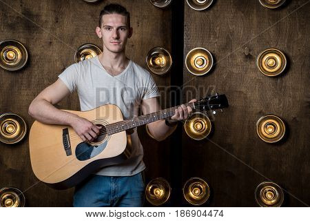 Guitarist, Music. A Young Man Plays An Acoustic Guitar On A Background With Lights Behind Him. Horiz