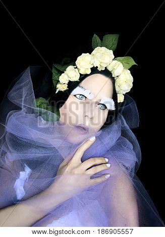 concept portrait of strange woman in white roses wreath with fantasy makeup
