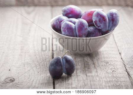 A bunch of Plums on a wooden table
