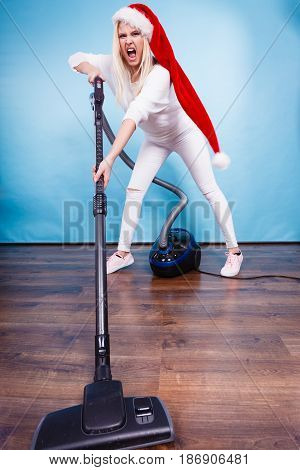 Woman vacuuming the house last minute. Teen girl in santa helper hat with vacuum cleaner angry furious face expression. Christmas time and housework concept.