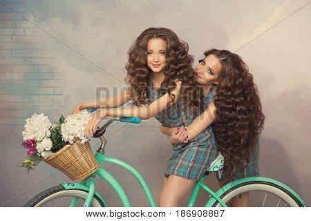 Women and a vintage bicycle. Two beautiful girls with long curly hair.