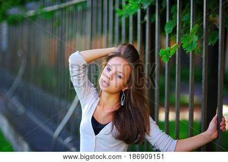 Portrait of young cute woman with a weary look holding hand behind bars wrought iron fence in a summer Park close-up