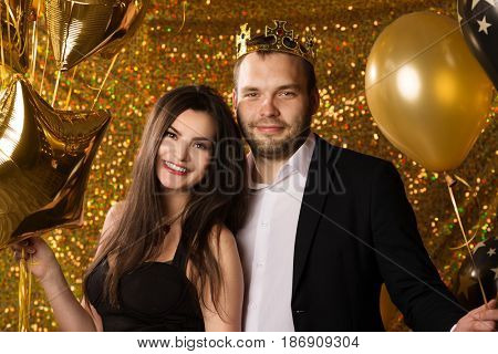 Couple at a party. Two, men and a woman celebrate the holiday. New Year or birthday. The guy and the girl have fun together. Romantic date