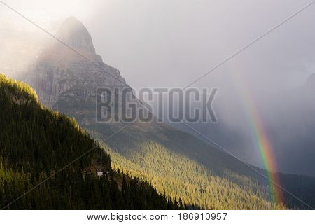 A storm passes over the center of Glacier National Park creating a rainbow