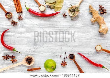 Spices, chili and herbs for cooking on wooden kitchen table background top view mock up