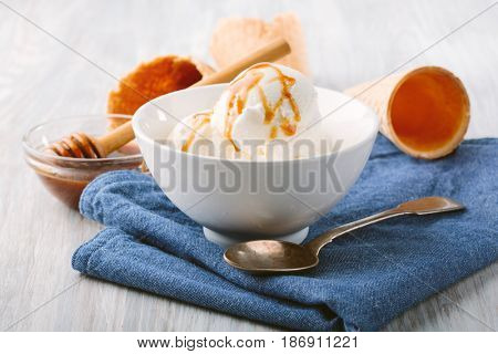 Vanilla ice cream with caramel in white bowl and waffle cones on the table