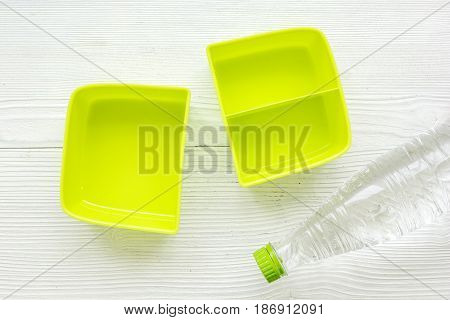 breakfast take away with green lunchbox and bottle on white wooden table background top view