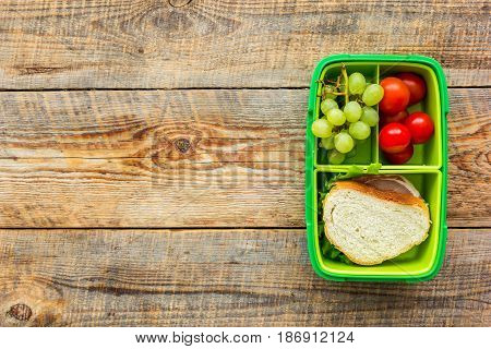 school lunch set with sandwich and vegetables in lunchbox on wooden table background top view mock up
