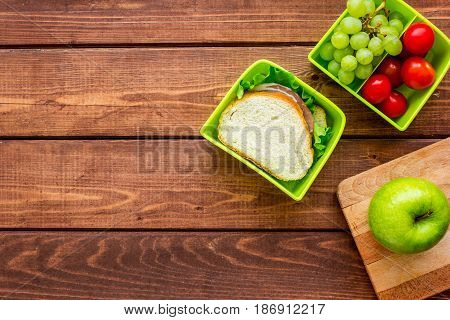 school lunch set with apple and vegetables in lunchbox on wooden table background top view mock up