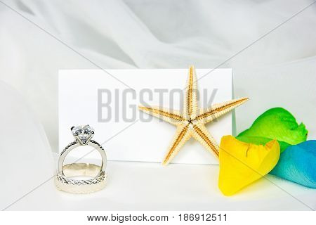 wedding rings and starfish on tulle with colorful rose petals and blank place card