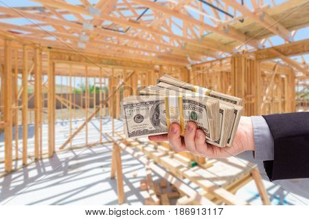 Hand With Stacks of Cash On Site Inside New Home Construction Framing.