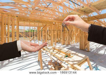 Handing Over The Keys On Site Inside New Home Construction Framing.