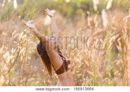 Asian woman wearing swimming suit enjoying sunlight and relaxing in a field