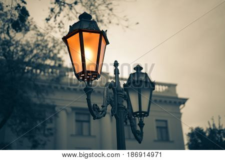 Black and white picture of Old Vintage street light with old building on background. Lamp light is colored.