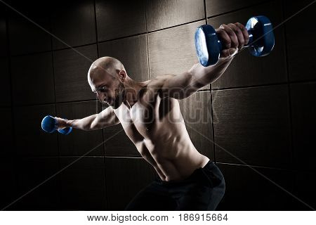Athletic muscular man training biceps with dumbbells on dark background