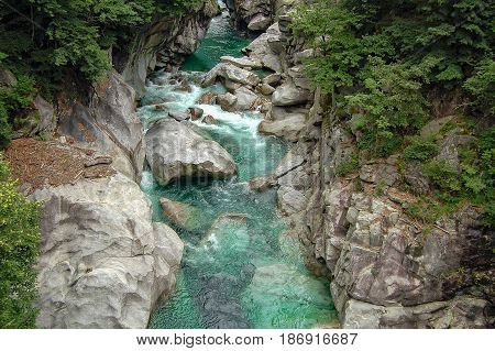 Emerald water of the Verzasca river polishes rocks strenously - Val Verzasca Switzerland