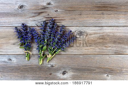 Three bundles of wild spring flowers on rustic wood. Flat lay view.